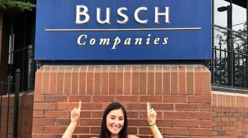 Josey Jagelski pointing at an Anheuser-Busch logo