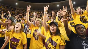 Students give the forks up sign at a basketball game at Wells Fargo Arena