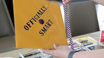 An ASU graduation cap that says Officially Smart