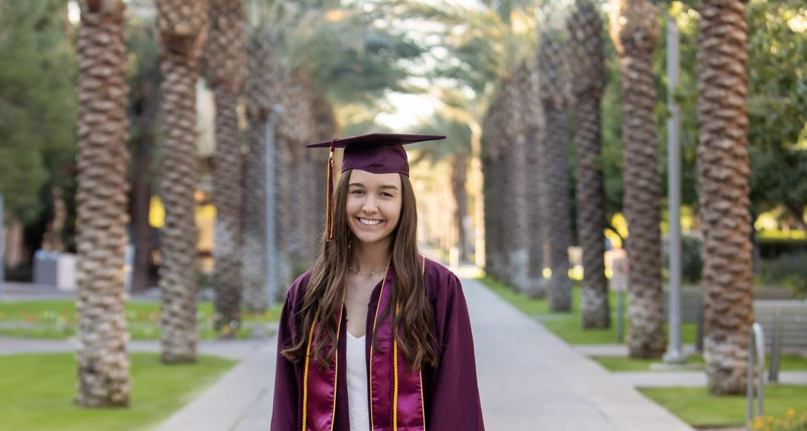 Graduate Claire Muranaka poses in her cap and gown on the palm walk at ASU.