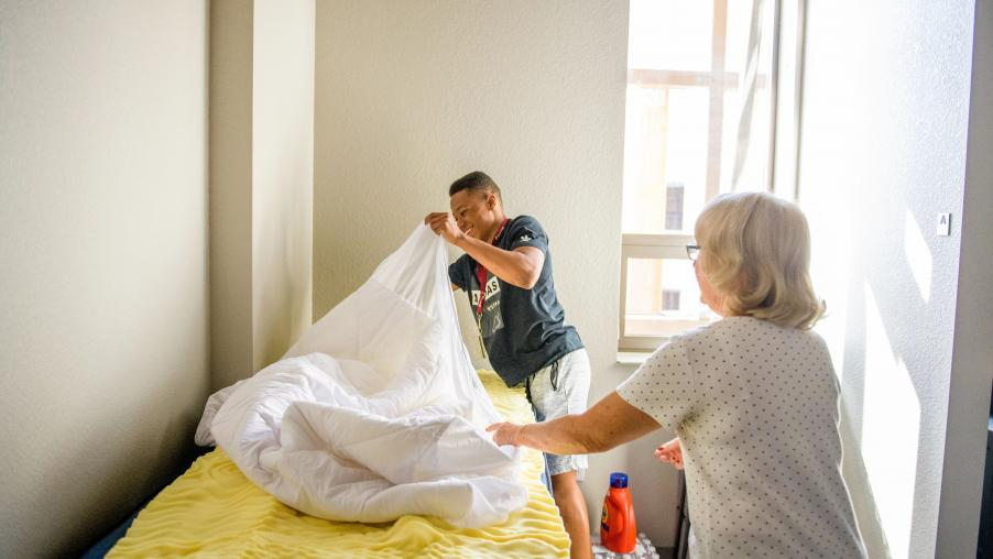 A student and parent making a bed in an ASU residence hall