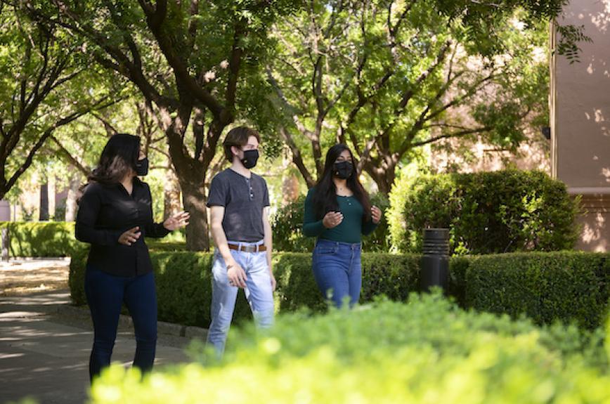Three ASU students walk while social distancing and wearing masks.