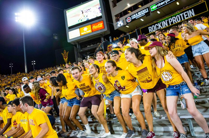 Students with their arms around each other in the ASU Inferno student section at Sun Devil Stadium