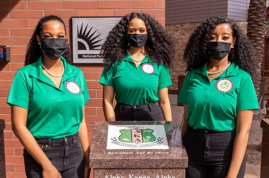 Members the Alpha Kappa Alpha Sorority at Arizona State University stand in front of their plot in the GLV.