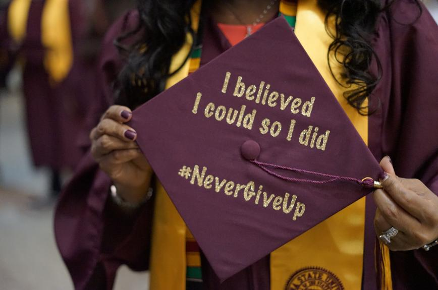 """ASU student holds up custom graduation cap reading """"I believed I could so I did #NeverGiveUp."""""""