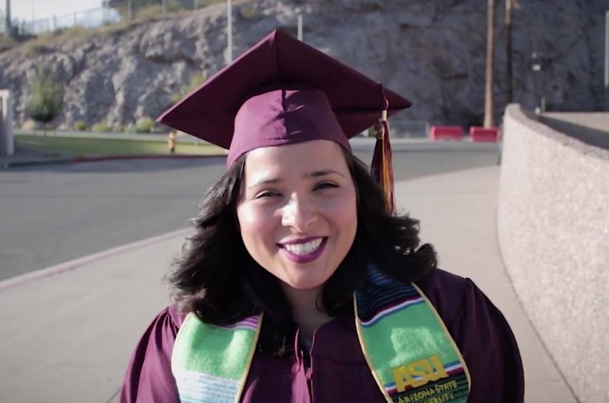 ASU student in a cap and gown near Wells Fargo Arena in Tempe wearing Hispanic convocation stole