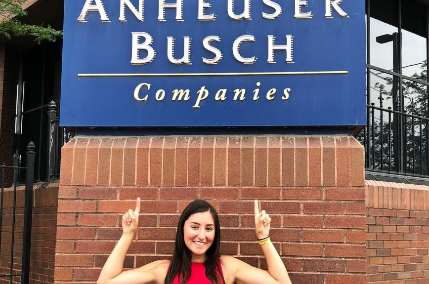 Josey Jagelski pointing at an Anheuser-Busch logo