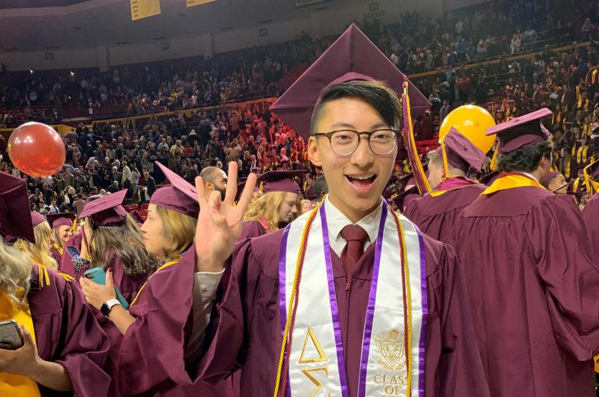 Bryan Pietsch doing a forks up symbol in his cap and gown at ASU graduation