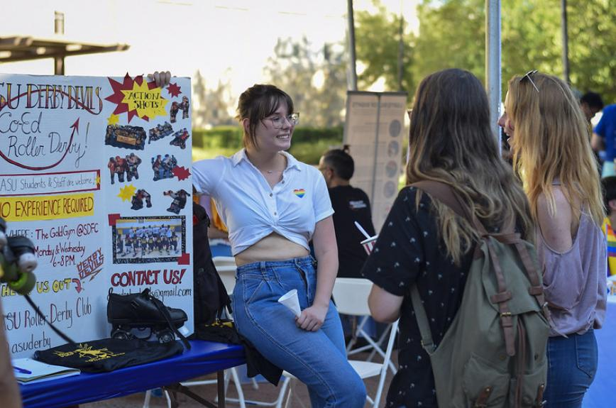 Students talk next to a roller derby poster