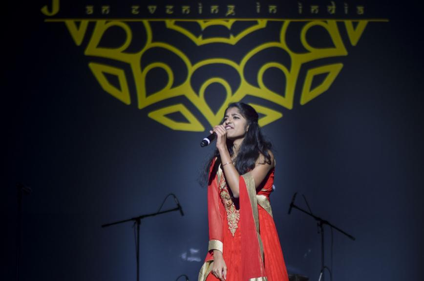 An ASU student singing on the Jhankaar stage in a red dress