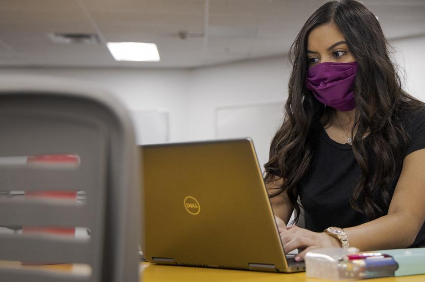 Female ASU student uses her computer while wearing a mask.