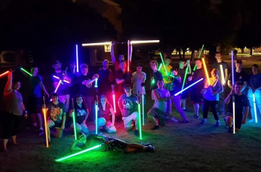 A group of ASU students with lit-up lightsabers at night
