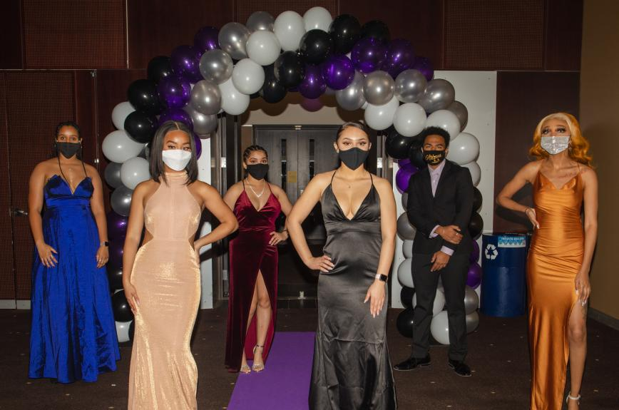Students in gowns and suits with masks on at the Black Excellence Ball at ASU Tempe