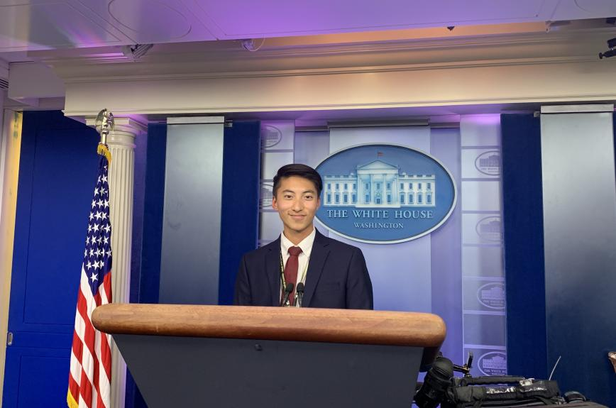 ASU Student Life Storyteller, Bryan Pietsch, poses at a podium in The White House