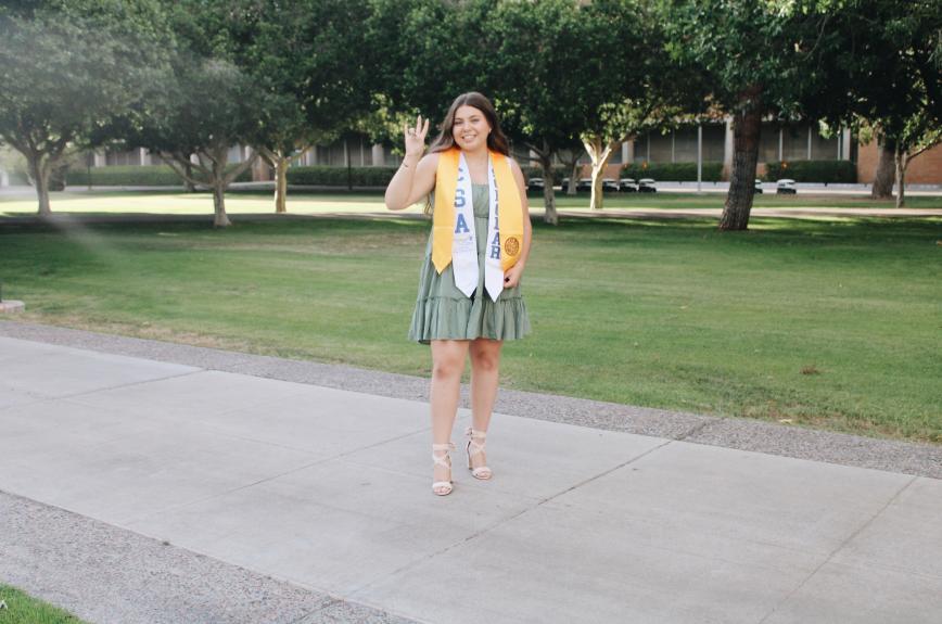 ASU Grad Carmen De Alba Cardenas holds up the pitchfork hand signal for a graduation photo.