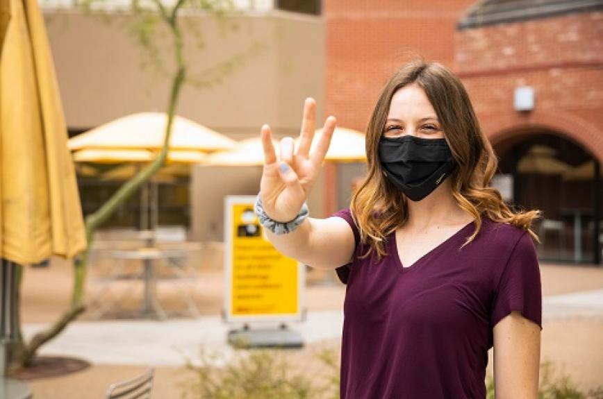 ASU student Madeleine Williamson giving a forks up wearing an ASU Community of Care kit mask