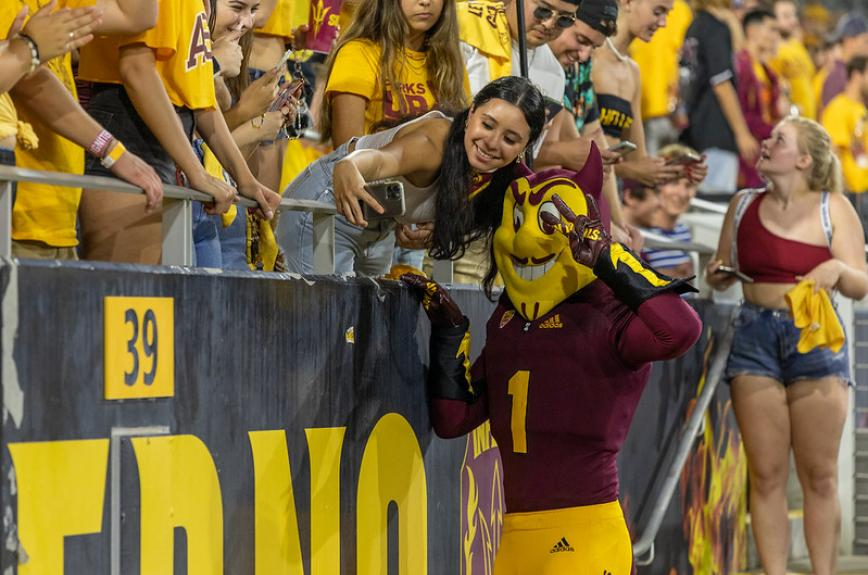 A fan in the football Inferno student section takes a selfie with Sparky