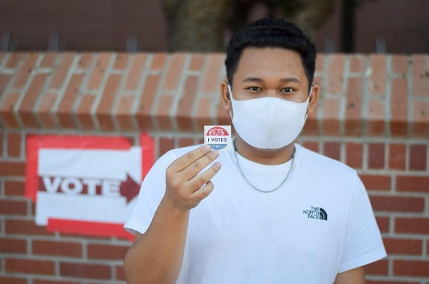 An ASU student tolds up an I voted sticker wearing a mask on Election Day Nov. 3 2020 at ASU Tempe