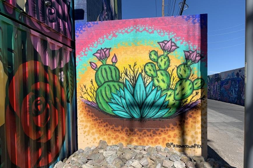 A brightly colored mural of a prickly pear cactus and aloe vera