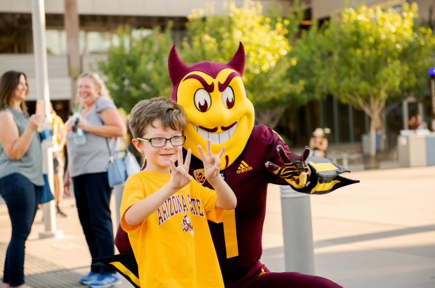 """Young child in ASU gear and sparky put their """"forks up."""""""