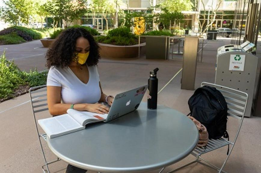 Student in a mask sitting in front of a laptop outside on ASU's Tempe campus
