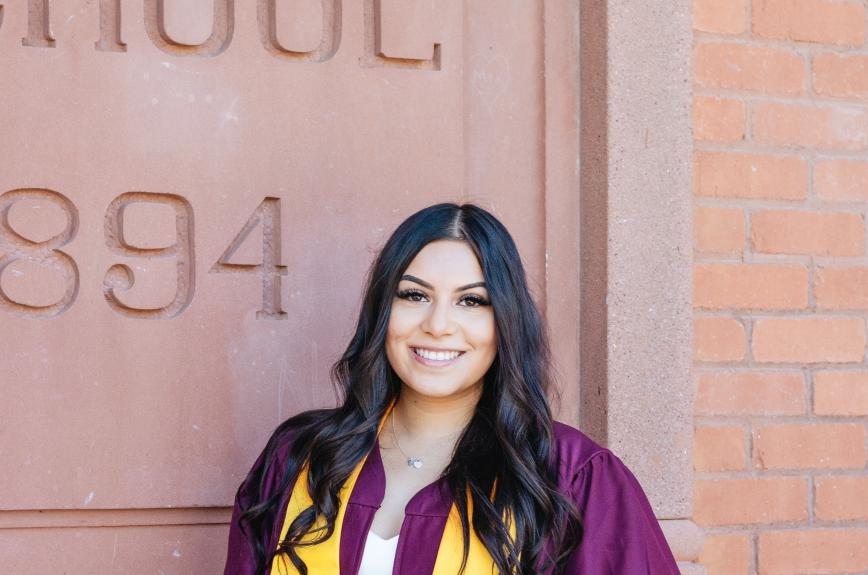 ASU grad Natalie Carranza smiles in her graduation gown in front of Old Main.