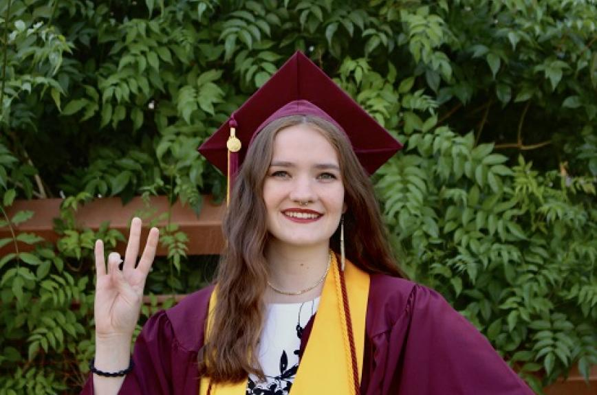 ASU grad Nora Thompson in her cap and gown giving a forks up sign