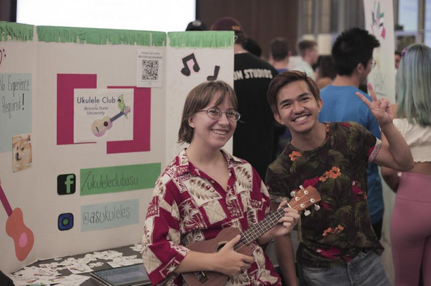 Two students in the Ukulele Club at ASU pose with the forks up hand symbol at Passport to ASU club fair fall 2019