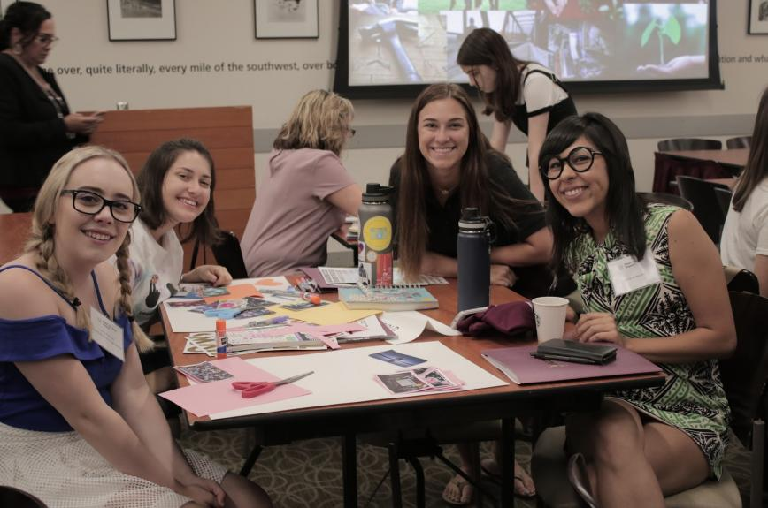 Young women participants at ASU peer to peer symposium smile at a table