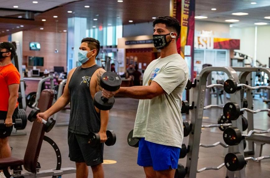 Two students in masks lift weights at the ASU Sun Devil Fitness Complex Downtown Phoenix