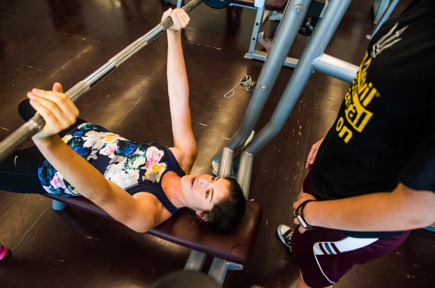 Woman does a bench press at ASU Sun Devil Fitness Complex