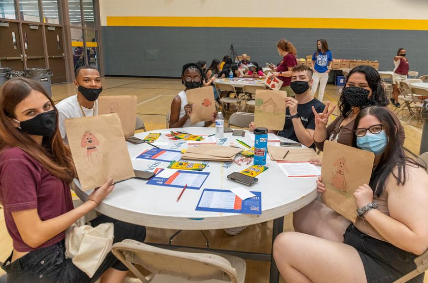 Students at a round table with masks on holding up bags with Clifford the dog drawn on them