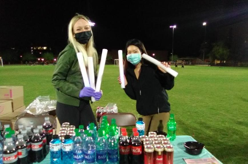 Two ASU students with masks and glow sticks on the SDFC Field