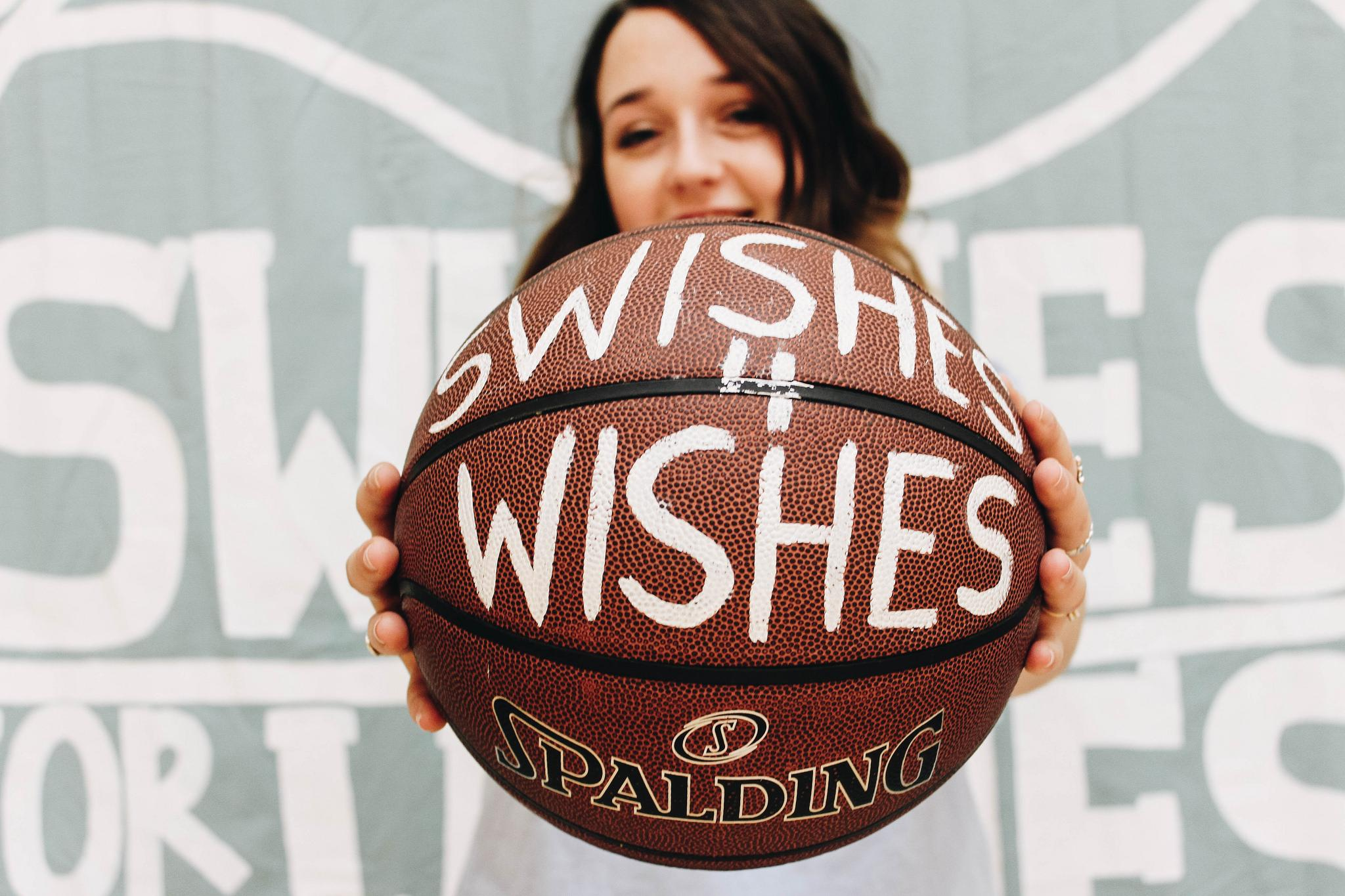 A woman holds a basketball up that says Swishes for Wishes in paint