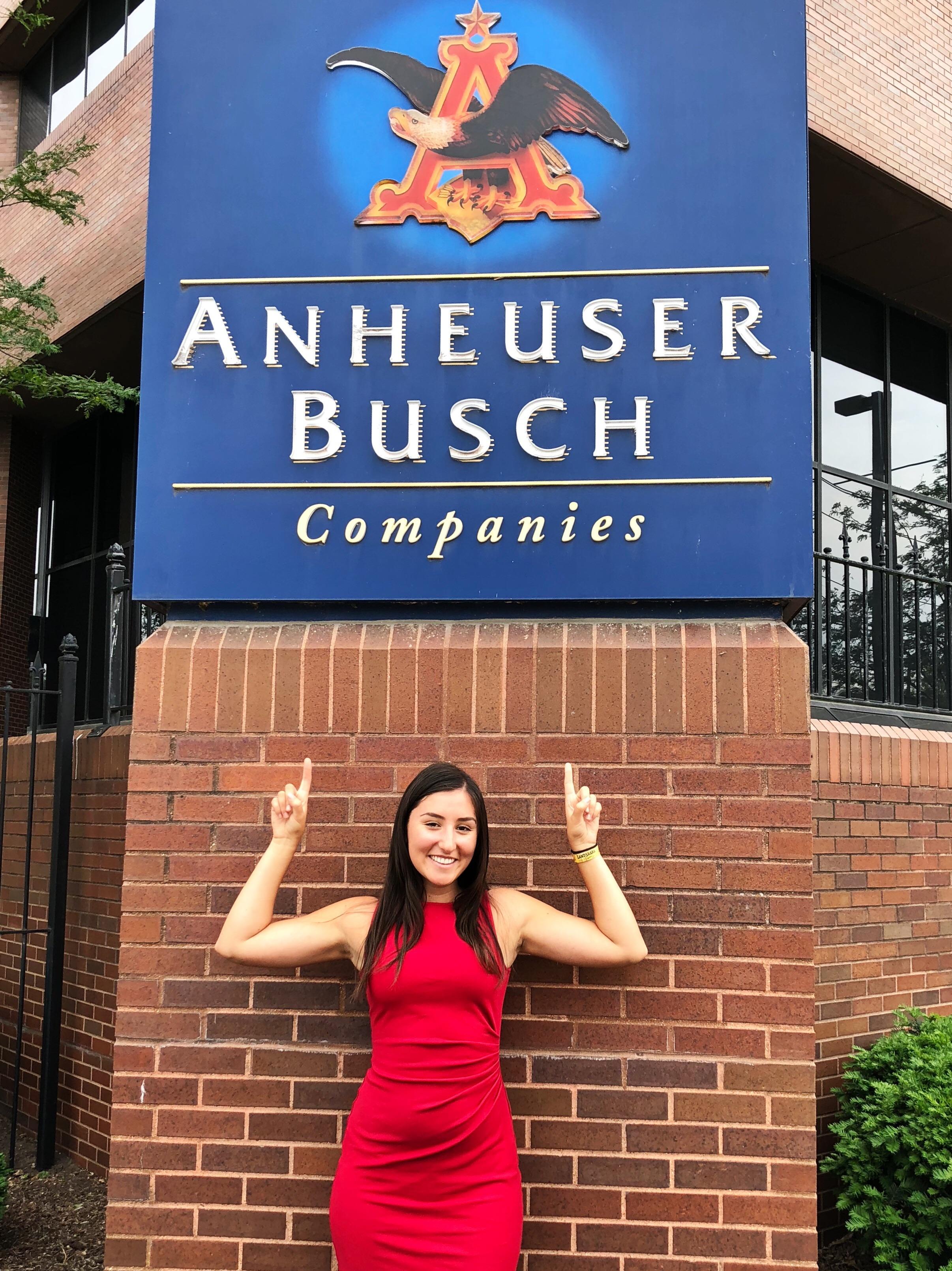 pointing at an Anheuser-Busch logo