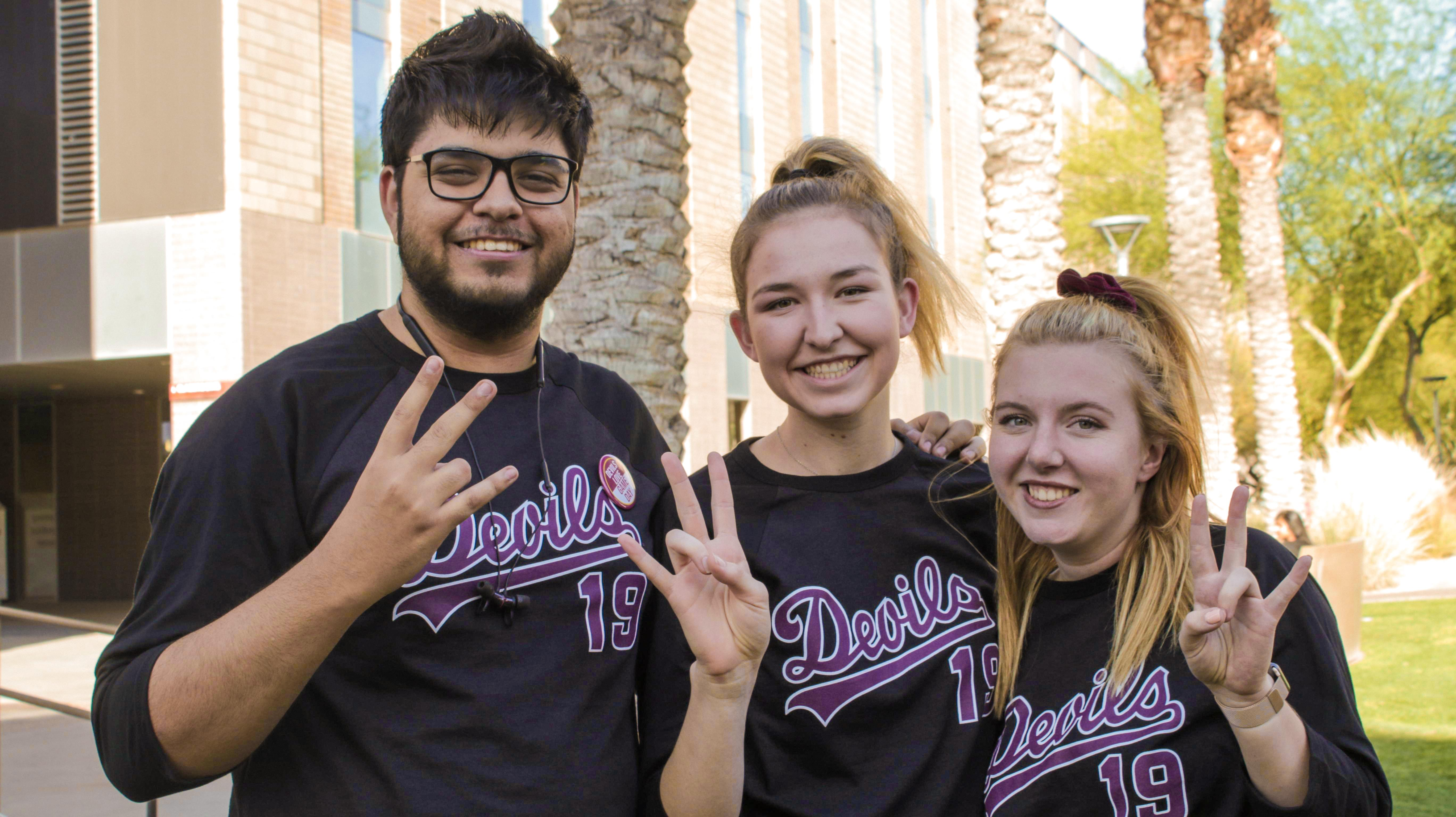 ASU students in baseball jerseys giving a forks up sign before the U of A games