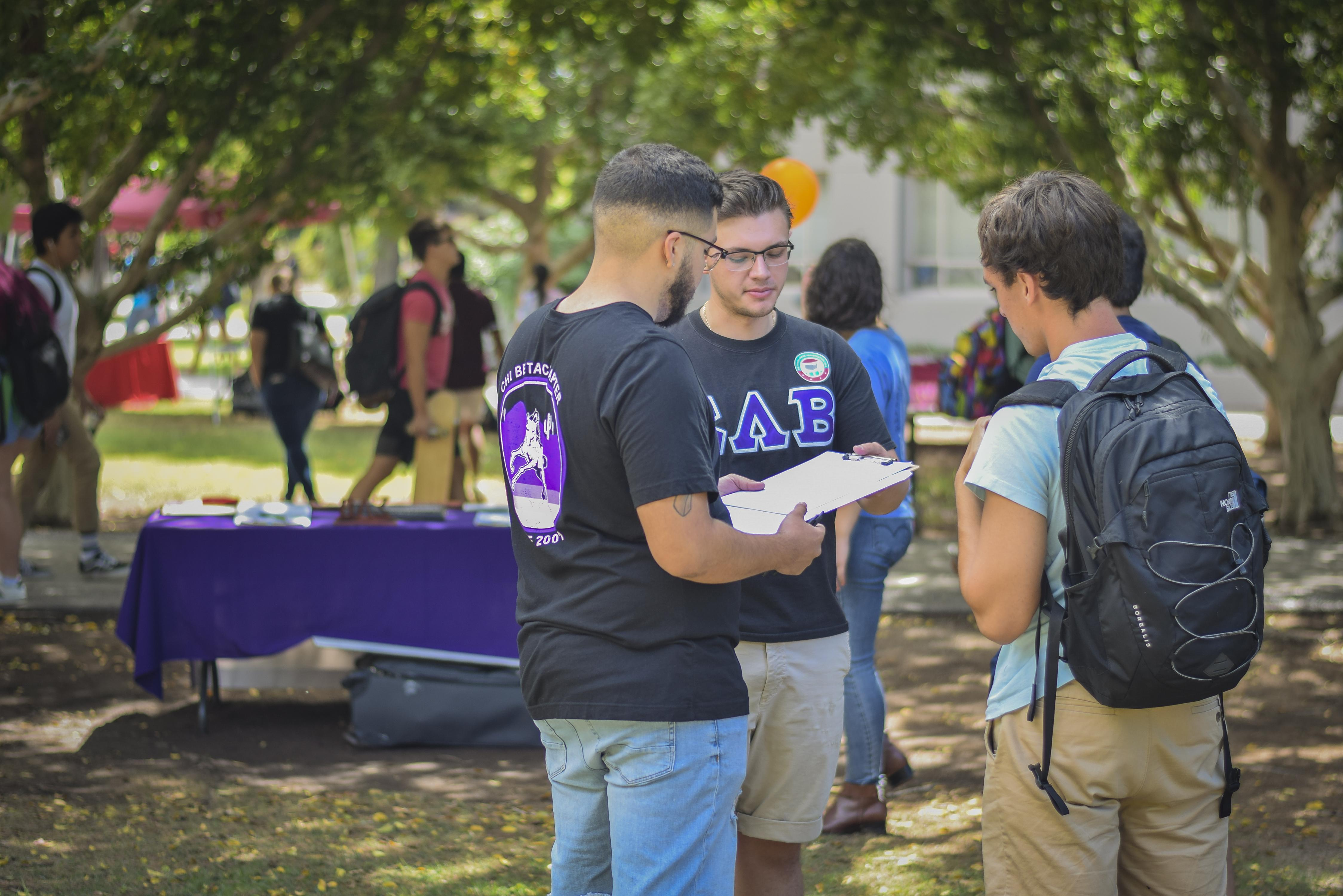 Three students, two with Greek-lettered shirts, talk with clipboards at National Voter Registration Day at ASU Tempe