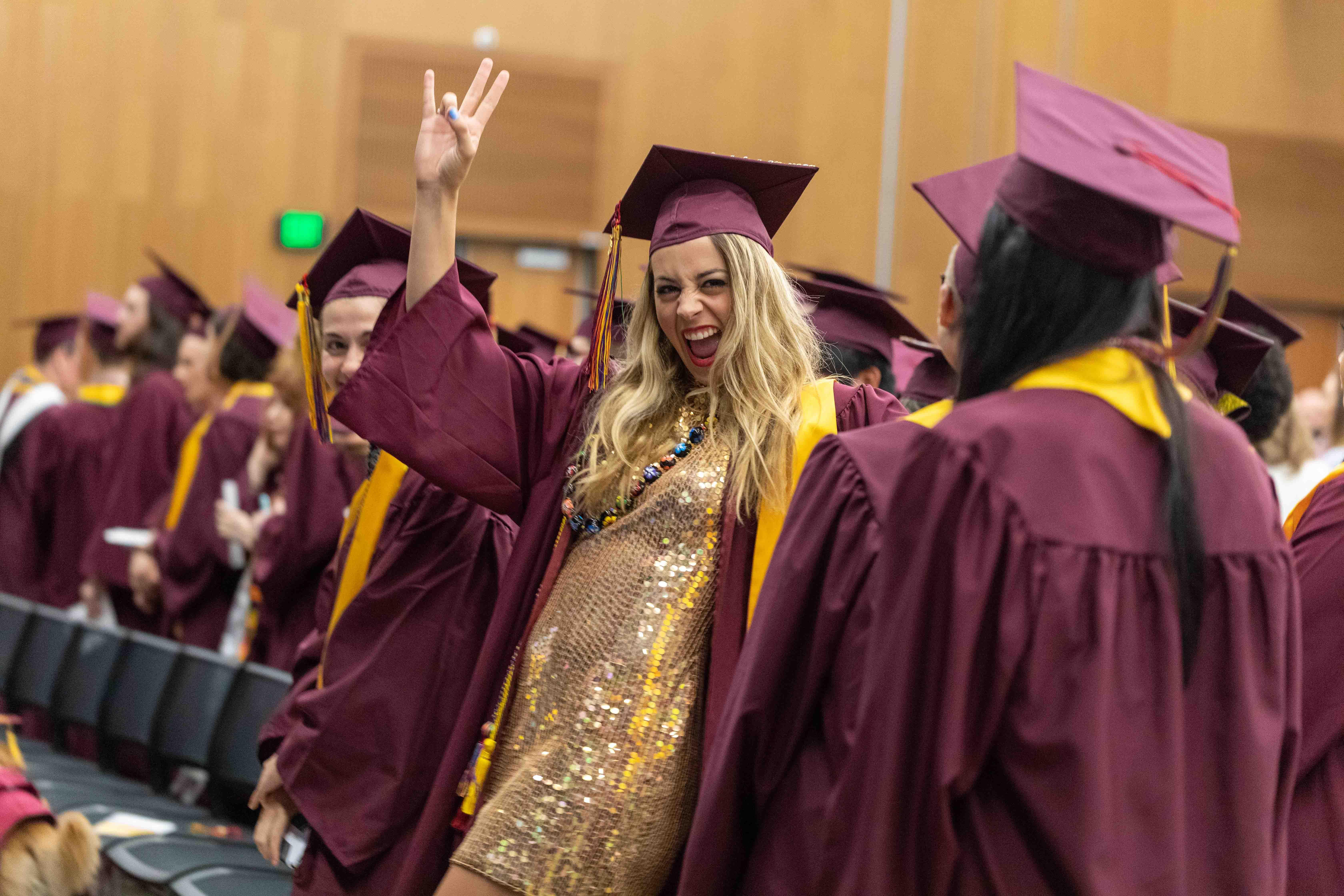 ASU student in a gold sequined dress gives a forks up symbol at the Rainbow LGBTQ graduation convocation at ASU's Tempe campus in the Student Pavilion