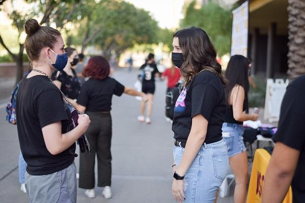 Two students in masks talking at ASU party at the polls
