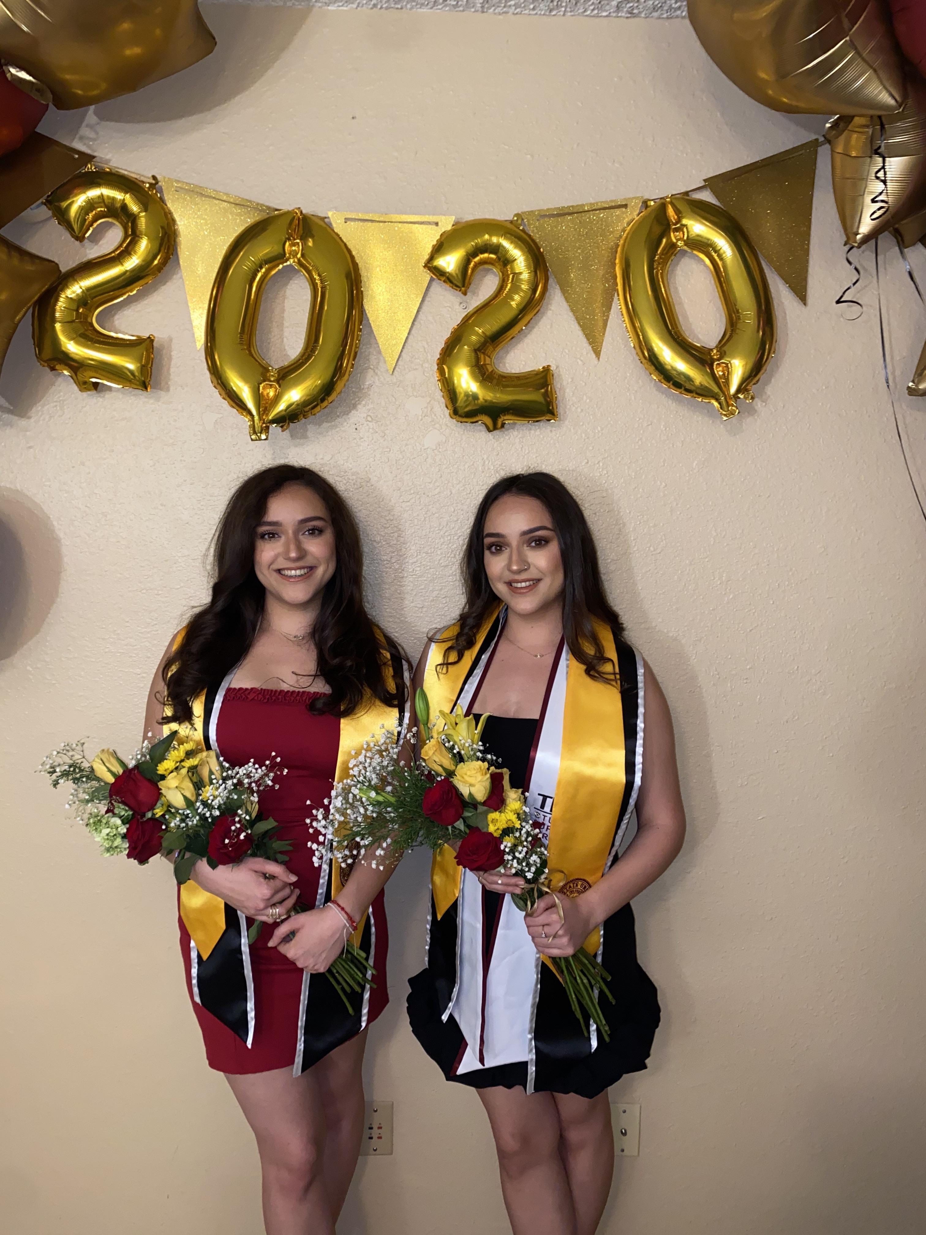 ASU twins Anahi and Sarahi Montano pose in front of graduation set up with balloons and flowers.