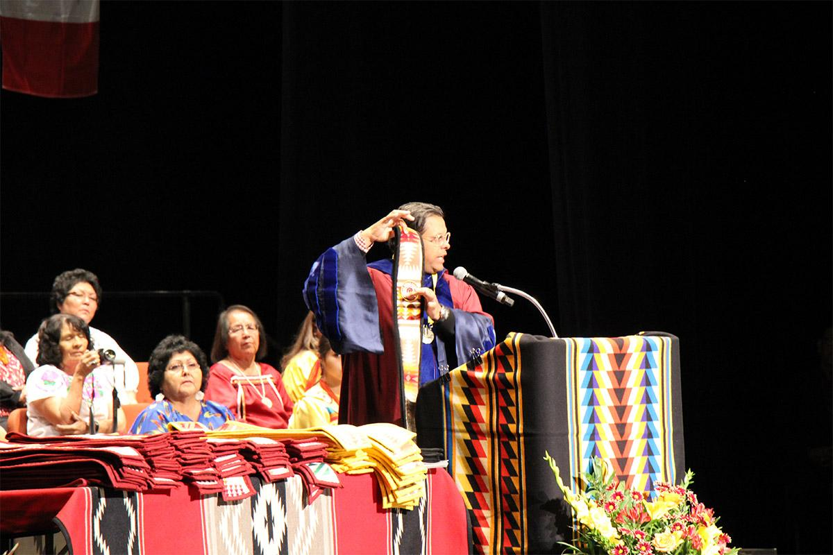 A speaker at the American Indian Convocation presents the American Indian graduation stole.