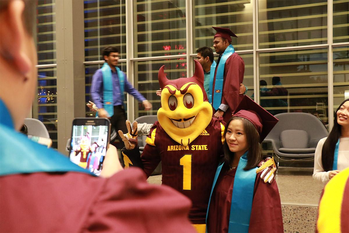 Sparky poses with a graduate of the International Student Convocation.