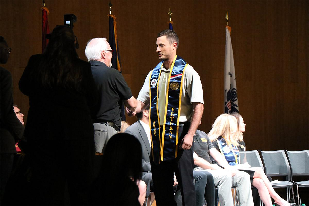 An Army veteran and Fall 2017 ASU graduate receives a congratulatory handshake at the Veterans Honor Stole ceremony.