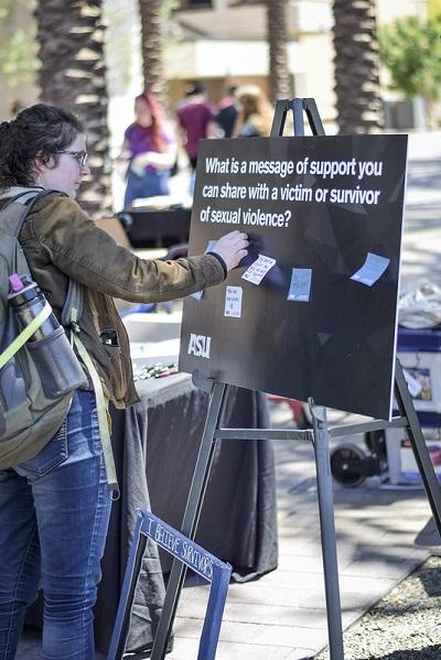 """A student places a post-it on a sign that says """"what is a message of support you an share with a victim or survivor of sexual violence?"""""""