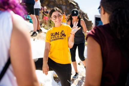 """A young woman with a palm painted white gives the ASU Sun Devils """"forks up"""" sign at """"A"""" Mountain while painting the """"A"""" white."""