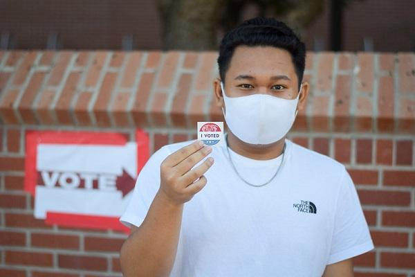 Student with an I voted sticker and a mask at the ASU Tempe campus