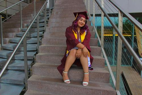 Gabriella Acosta in her ASU cap and gown sitting on steps