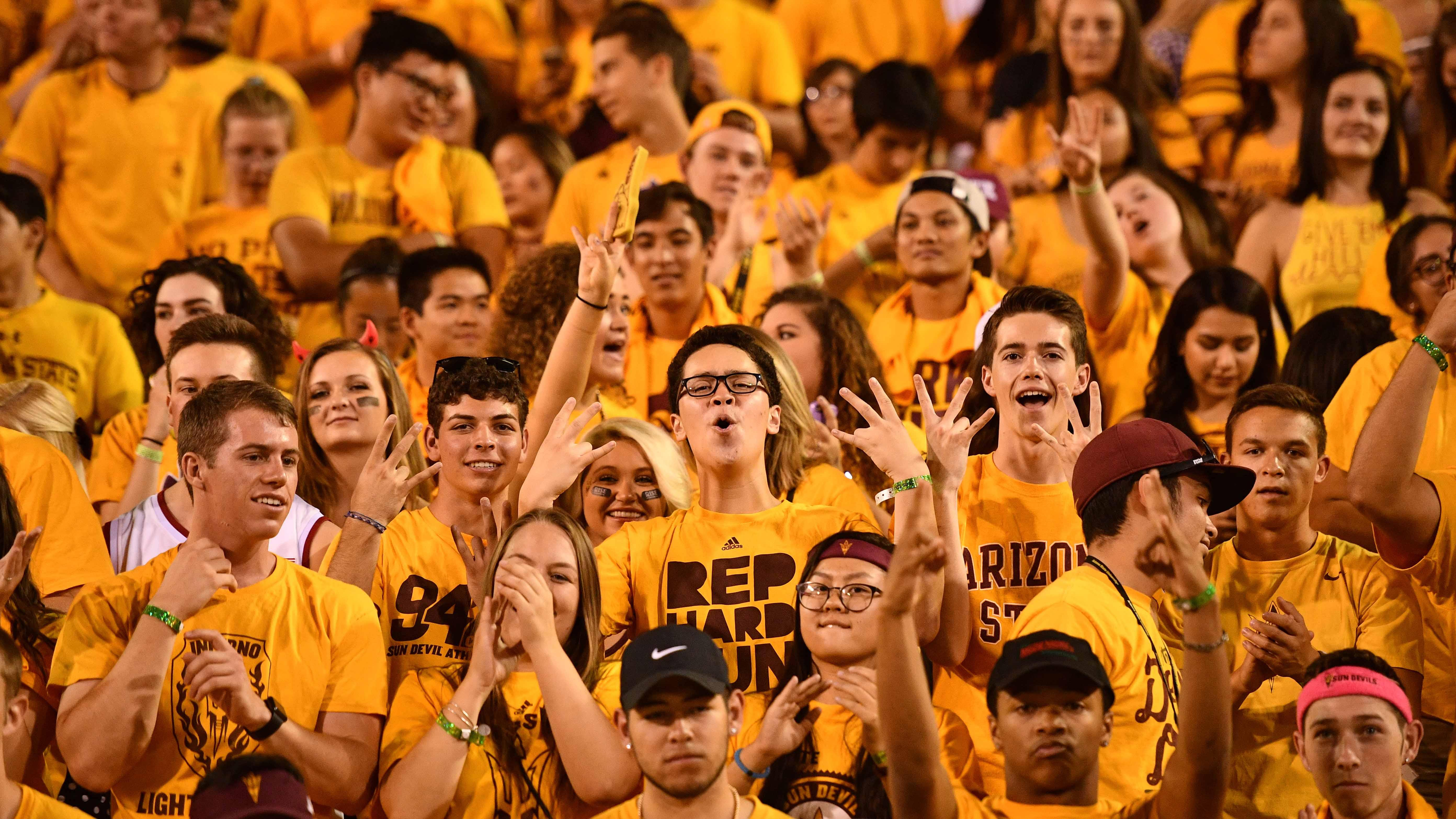 Students wear gold in the Inferno student section at Sun Devil Stadium for a football game