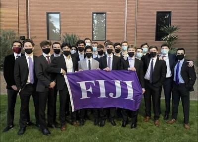 About 30 young men in suits and masks with a purple flag that says FIJI