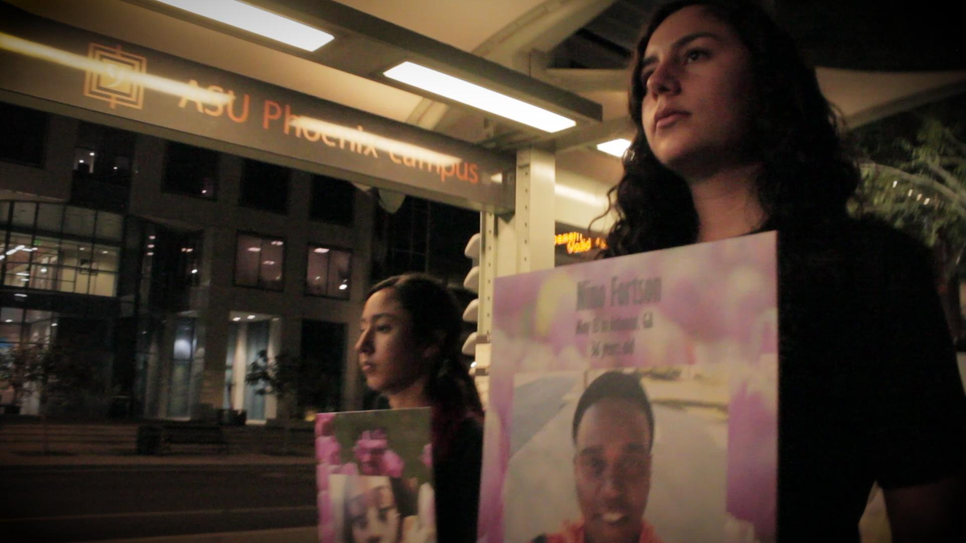 Students walk holding pictures of trans community members who were killed in 2018